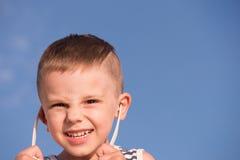 Lächelnder kleiner Junge des Bonbons, der Sonnenbrille auf Hintergrund des blauen Himmels entfernt Lizenzfreie Stockfotos