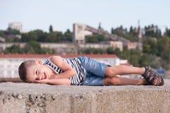 Lächelnder kleiner Junge liegt auf einem Betonblock auf einem Hintergrund von Hafengebäuden Lizenzfreies Stockbild