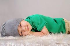 Lächelnder kleiner Junge liegt auf Pelz lizenzfreie stockfotos