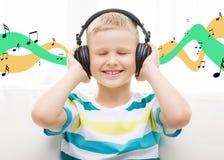 Lächelnder kleiner Junge mit Kopfhörern zu Hause Stockfotografie