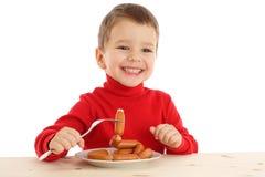 Lächelnder kleiner Junge mit Würsten auf Gabel Stockfotografie
