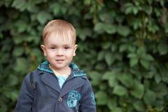 Lächelnder kleiner Junge steht nahen Baum Stockfotografie