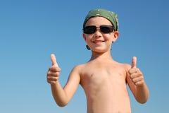Lächelnder kleiner Junge stellt O.K. auf dem Himmelhintergrund dar Stockfoto