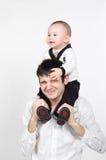 Lächelnder kleiner Sohn der jungen Vaterholding auf seinem sho stockfotos