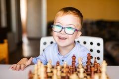 Lächelnder Kleinkindjunge mit Down-Syndrom mit den großen blauen Gläsern, die Schach im Kindergarten spielen stockfotos