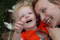 Lächelnder Kleinkindjunge streichelt draußen auf Decke mit der hübschen Mutter, die auf den Himmel zeigt Stockbild