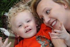 Lächelnder Kleinkindjunge streichelt draußen auf Decke mit hübscher Mutter Stockfotos