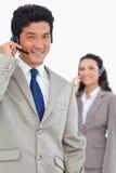 Lächelnder Kundenbetreuungsangestellter mit Kollegen Stockfotografie