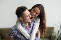 Lächelnder lachender umfassender junger Ehemann der Frau, der sie a huckepack trägt lizenzfreies stockbild