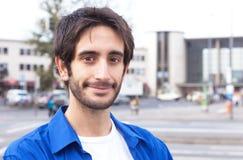Lächelnder lateinischer Kerl in einem blauen Hemd in der Stadt Lizenzfreies Stockfoto