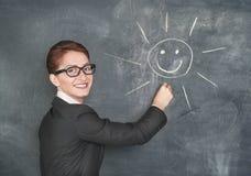 Lächelnder Lehrer, der eine glückliche Sonne malt Lizenzfreie Stockfotos