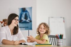 Lächelnder Lehrer und glückliches Kind, die Hausarbeit nach Klassen tun lizenzfreie stockbilder