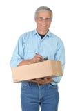 Lächelnder Lieferbote mit Paket und Klemmbrett Stockfotografie