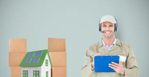 Lächelnder Lieferer, der Klemmbrett durch Haus und Pakete hält Stockfotos