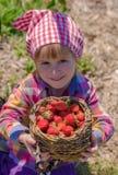 Lächelnder Mädchengriffkorb voll von Erdbeeren Stockfotografie