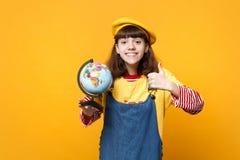 Lächelnder Mädchenjugendlicher in französischen Barett und Denim sundress, die sich Daumen, Erdweltkugel halten lokalisiert auf G lizenzfreie stockbilder