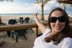 Lächelnder Mädchenpunkt zum Seestrand Lizenzfreie Stockfotografie