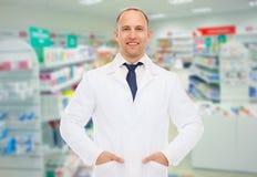 Lächelnder männlicher Apotheker im weißen Mantel am Drugstore lizenzfreie stockbilder