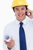 Lächelnder männlicher Architekt auf seinem Mobiltelefon Stockbild