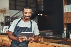Lächelnder männlicher Caféinhaber, der digitale Tablette betrachtet stockfoto