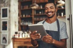 Lächelnder männlicher Caféinhaber, der digitale Tablette in seiner Hand hält lizenzfreies stockfoto