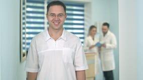 Lächelnder männlicher Doktor in den Gläsern, die Kamera während medizinisches Personal arbeitet an dem Hintergrund betrachten stock footage
