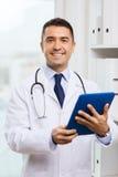 Lächelnder männlicher Doktor im weißen Mantel mit Tabletten-PC stockfotos