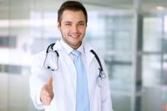 Lächelnder männlicher Doktor ist zum Händedruck bereit Lizenzfreie Stockbilder