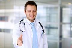 Lächelnder männlicher Doktor ist zum Händedruck bereit Stockfoto