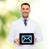 Lächelnder männlicher Doktor mit Tabletten-PC Stockbild