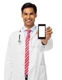 Lächelnder männlicher Doktor Showing Smart Phone Lizenzfreie Stockfotos