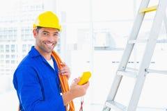 Lächelnder männlicher Elektriker, der Vielfachmessgerät im Büro hält lizenzfreies stockfoto