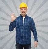 Lächelnder männlicher Erbauer im Sturzhelm, der okayzeichen zeigt Stockfotografie
