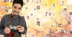 Lächelnder männlicher Fotograf, der Kamera gegen Fliegenporträts hält Stockbilder