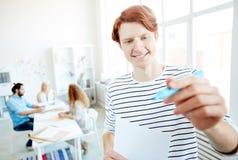 Lächelnder männlicher Manager, der Informationen für Darstellung vorbereitet stockfoto