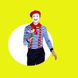 Lächelnder männlicher Pantomime mit Blumen Lustiger Schauspieler im Rot Stockfotos