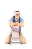 Lächelnder männlicher Student mit der Schultasche, die nahe einem Stapel von Büchern aufwirft Lizenzfreies Stockfoto