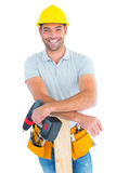 Lächelnder männlicher Tischler mit Bohrmaschine und Planke lizenzfreie stockfotografie