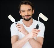 Lächelnder Maler, der eine Rolle und eine Bürste hält Stockfotografie