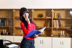 Lächelnder Manager in einer roten Bluse mit einem Ordner von Dokumenten Stockbild