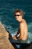 Lächelnder Mann auf dem Felsen Stockbilder