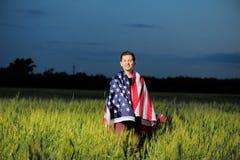 Lächelnder Mann auf einem Weizengebiet mit amerikanischer Flagge Stockbilder