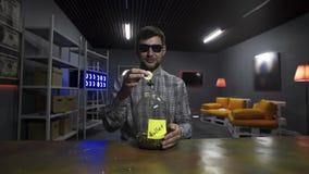 Lächelnder Mann Blogger lässt großes Gold-bitcoin in Glasgefäß vor Kamera fallen stock video