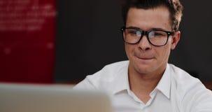 Lächelnder Mann in den Gläsern arbeitet an seinem Laptop im Büro stock video