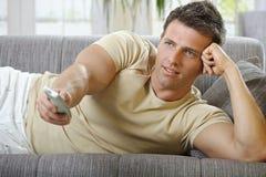 Lächelnder Mann, der auf überwachendem Fernsehen des Sofas liegt stockfotografie