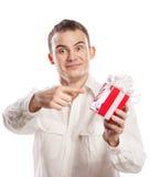 Lächelnder Mann, der auf das Geschenk getrennt auf Weiß zeigt stockbild