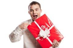 Lächelnder Mann, der auf das Geschenk getrennt auf Weiß zeigt stockfotografie