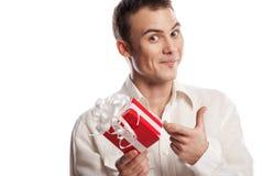 Lächelnder Mann, der auf das Geschenk getrennt zeigt stockfotos