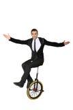 Lächelnder Mann, der auf einem Unicycle sitzt isolat Lizenzfreie Stockbilder