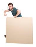 Lächelnder Mann, der auf leeres Plakat zeigt Stockfotografie